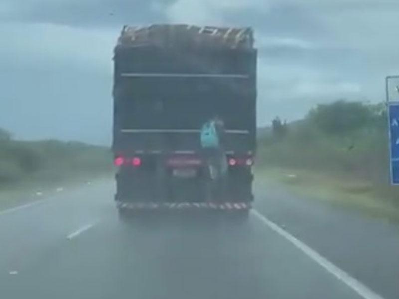 Homem é flagrado viajando pendurado em carreta sob forte chuva na Bahia